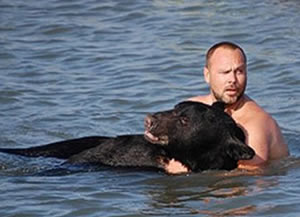 Biologist Adam Warwick saves black bear